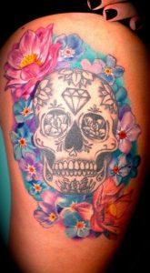 Tatuaggio di calavera messicana con diamante sulla fronte e corona di fiori