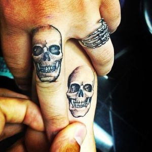 Tatuaggio con due teschi sulle dita