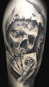 Tatuaggio con teschio della morte incappucciato e carte da gioco