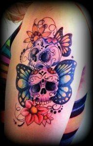 Tatuaggio con teschi messicani e farfalle in testa